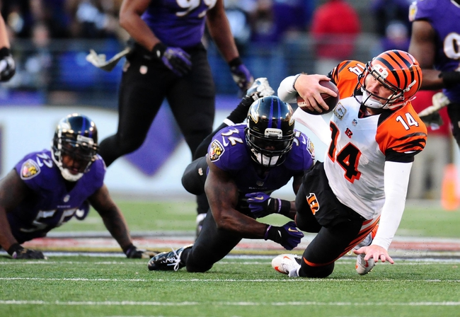 Nov 10, 2013; Baltimore, MD, USA; Cincinnati Bengals quarterback Andy Dalton (14) is tackled by Baltimore Ravens safety James Ihedigbo (32) at M&T Bank Stadium. Mandatory Credit: Evan Habeeb-USA TODAY Sports