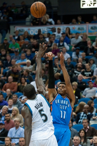 Nov 1, 2013; Minneapolis, MN, USA; Oklahoma City Thunder shooting guard Jeremy Lamb (11) shoots against Minnesota Timberwolves center Gorgui Dieng (5) in the fourth quarter at Target Center. Timberwolves won 100-81. Mandatory Credit: Greg Smith-USA TODAY Sports