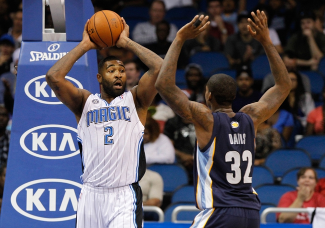 Oct 18, 2013; Orlando, FL, USA; Orlando Magic power forward Kyle O'Quinn (2) passes the ball past Memphis Grizzlies power forward Ed Davis (32) during the second half at Amway Center. Memphis Grizzlies defeated the Orlando Magic 97-91. Mandatory Credit: Kim Klement-USA TODAY Sports
