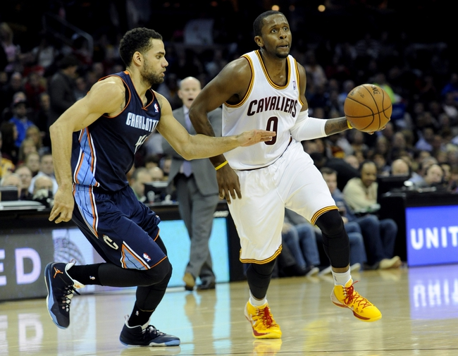 Nov 15, 2013; Cleveland, OH, USA; Cleveland Cavaliers shooting guard C.J. Miles (0) and Charlotte Bobcats shooting guard Jeff Taylor (44) at Quicken Loans Arena. Mandatory Credit: Ken Blaze-USA TODAY Sports