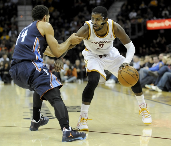 Nov 15, 2013; Cleveland, OH, USA; Charlotte Bobcats shooting guard Jeff Taylor (44) grabs Cleveland Cavaliers point guard Kyrie Irving (2) at Quicken Loans Arena. Mandatory Credit: Ken Blaze-USA TODAY Sports