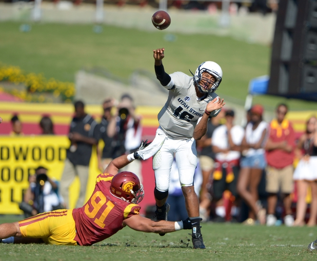 Sep 21, 2013; Los Angeles, CA, USA; Utah State Aggies quarterback Chuckie Keeton (16) is pressured by Southern California Trojans linebacker Morgan Breslin (91) at the Los Angeles Memorial Coliseum. USC defeated Utah State 17-14. Mandatory Credit: Kirby Lee-USA TODAY Sports