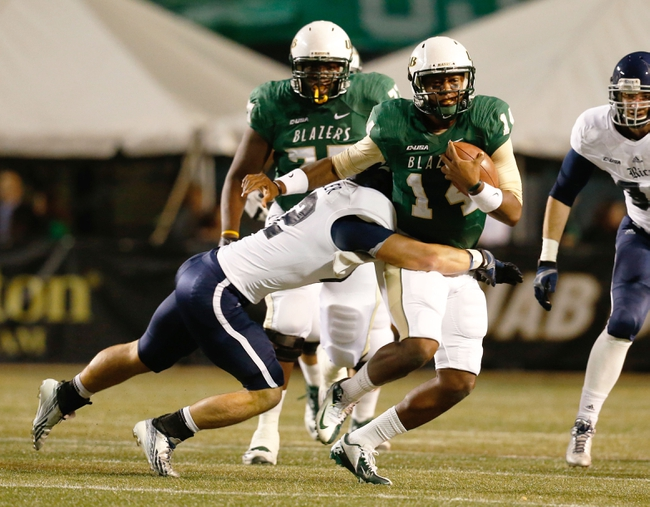 Nov 21, 2013; Birmingham, AL, USA;  UAB Blazers quarterback Jonathan Perry (14) is tackeld by Rice Owls linebacker Michael Kutzler (42) at Legion Field. Mandatory Credit: Marvin Gentry-USA TODAY Sports