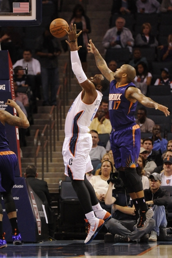 Nov 22, 2013; Charlotte, NC, USA; Charlotte Bobcats center Al Jefferson (25) and Phoenix Suns forward guard P.J. Tucker (17) fight for a rebound during the first half of the game at Time Warner Cable Arena. Mandatory Credit: Sam Sharpe-USA TODAY Sports