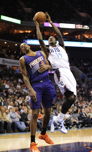 Nov 22, 2013; Charlotte, NC, USA; Charlotte Bobcats forward Michael Kidd-Gilchrist (14) drives into Phoenix Suns forward center Channing Frye (8) during the game at Time Warner Cable Arena. Suns win 98-91. Mandatory Credit: Sam Sharpe-USA TODAY Sports