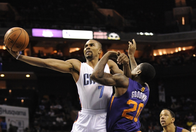 Nov 22, 2013; Charlotte, NC, USA; Charlotte Bobcats guard Ramon Sessions (7) drives to the basket as he is defended by Phoenix Suns guard Archie Goodwin (20) during the second half of the game at Time Warner Cable Arena. Suns win 98-91. Mandatory Credit: Sam Sharpe-USA TODAY Sports
