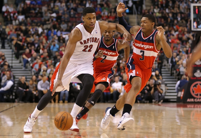 Nov 22, 2013; Toronto, Ontario, CAN; Toronto Raptors forward Rudy Gay (22) drives to the basket against Washington Wizards shooting guard Bradley Beal (3) and point guard John Wall (2) at Air Canada Centre. The Raptors beat the Wizards 96-88. Mandatory Credit: Tom Szczerbowski-USA TODAY Sports