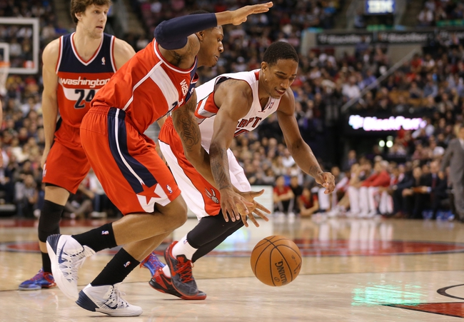 Nov 22, 2013; Toronto, Ontario, CAN; Washington Wizards shooting guard Bradley Beal (3) battles for the ball against Toronto Raptors guard DeMar DeRozan (10) at Air Canada Centre. The Raptors beat the Wizards 96-88. Mandatory Credit: Tom Szczerbowski-USA TODAY Sports