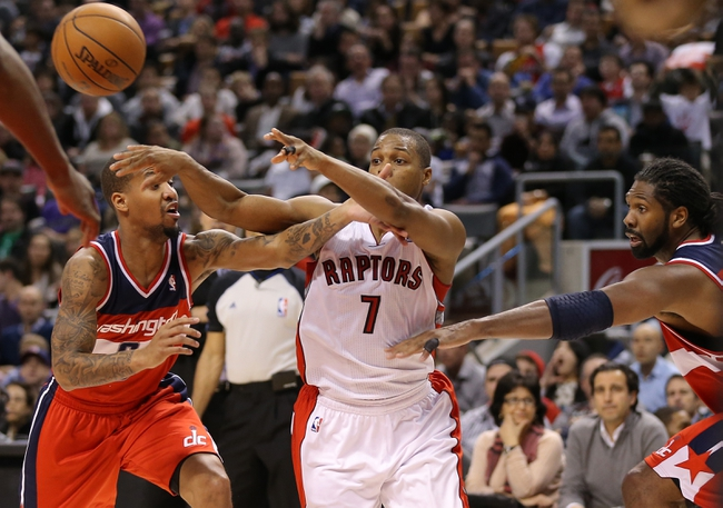 Nov 22, 2013; Toronto, Ontario, CAN; Toronto Raptors point guard Kyle Lowry (7) passes under pressure from Washington Wizards guard Eric Maynor (6) and forward Nene (42) at Air Canada Centre. The Raptors beat the Wizards 96-88. Mandatory Credit: Tom Szczerbowski-USA TODAY Sports