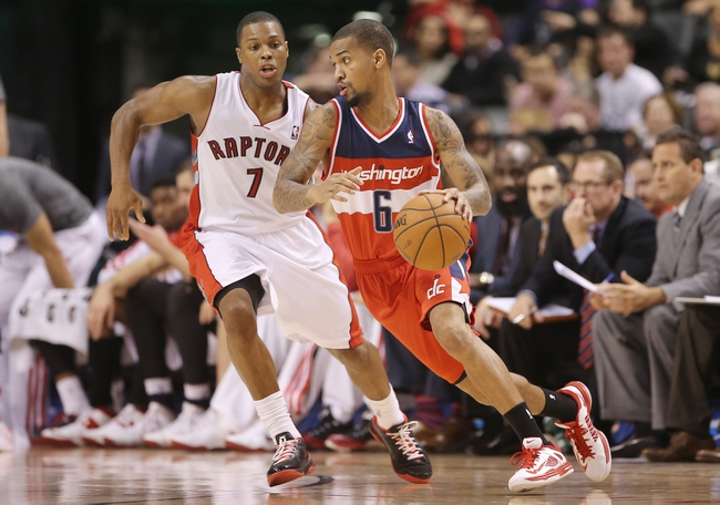 Nov 22, 2013; Toronto, Ontario, CAN; Washington Wizards guard Eric Maynor (6) makes a move as he is guarded by Toronto Raptors point guard Kyle Lowry (7) at Air Canada Centre. The Raptors beat the Wizards 96-88. Mandatory Credit: Tom Szczerbowski-USA TODAY Sports