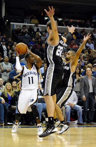 Nov 22, 2013; Memphis, TN, USA; Memphis Grizzlies point guard Mike Conley (11) is guarded by San Antonio Spurs center Tiago Splitter (22) and  point guard Tony Parker (9) during the fourth quarter at FedExForum. San Antonio Spurs beat the Memphis Grizzlies 102-86. Mandatory Credit: Justin Ford-USA TODAY Sports
