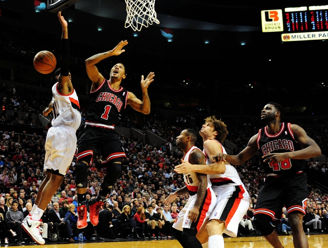 Nov 22, 2013; Portland, OR, USA; Chicago Bulls point guard Derrick Rose (1) is fouled by Portland Trail Blazers power forward LaMarcus Aldridge (12) as he drives to the basket during the first quarter of the game at the Moda Center. Mandatory Credit: Steve Dykes-USA TODAY Sports