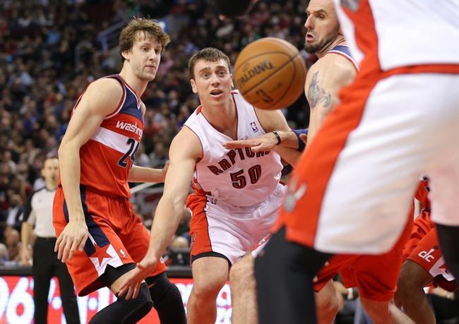 Nov 22, 2013; Toronto, Ontario, CAN; Toronto Raptors forward Tyler Hansbrough (50) passes the ball as Washington Wizards center Marcin Gortat (4) defends at Air Canada Centre. The Raptors beat the Wizards 96-88. Mandatory Credit: Tom Szczerbowski-USA TODAY Sports