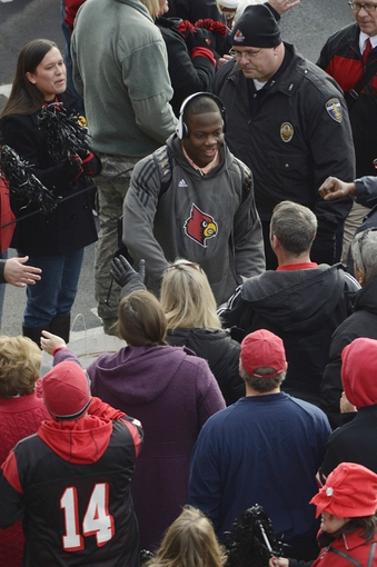 Nov 23, 2013; Louisville, KY, USA; Louisville Cardinals quarterback Teddy Bridgewater (5) greets fans during the Card March before the start of game against the Memphis Tigers at Papa Johns Cardinal Stadium. Mandatory Credit: Jamie Rhodes-USA TODAY Sports