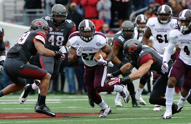Nov 23, 2013; Little Rock, AR, USA; Mississippi State Bulldogs running back LaDarius Perkins (27) carries the ball while being chased by Arkansas Razorbacks safety Price Holmes (15) at War Memorial Stadium. Mandatory Credit: Justin Ford-USA TODAY Sports