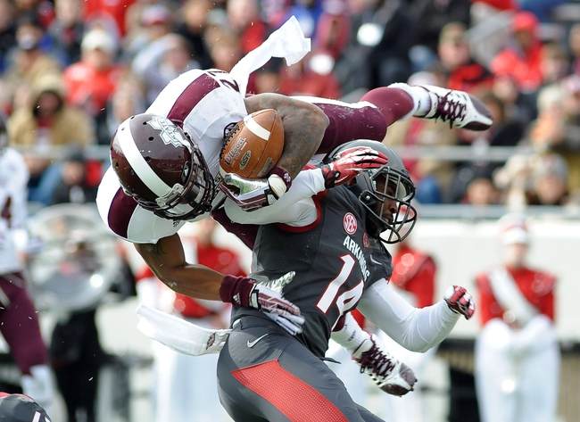 Nov 23, 2013; Little Rock, AR, USA; Mississippi State Bulldogs running back LaDarius Perkins (27)  dives into the end zone against Arkansas Razorbacks safety Eric Bennett (14)  during the second quarter at War Memorial Stadium. Mandatory Credit: Justin Ford-USA TODAY Sports