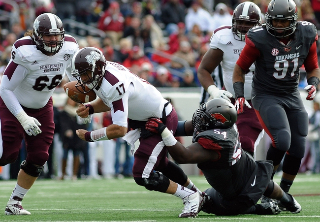 Nov 23, 2013; Little Rock, AR, USA; Mississippi State Bulldogs quarterback Tyler Russell (17)  loses the ball while tackled by Arkansas Razorbacks defensive tackle Byran Jones (54) during the second quarter at War Memorial Stadium. Mandatory Credit: Justin Ford-USA TODAY Sports