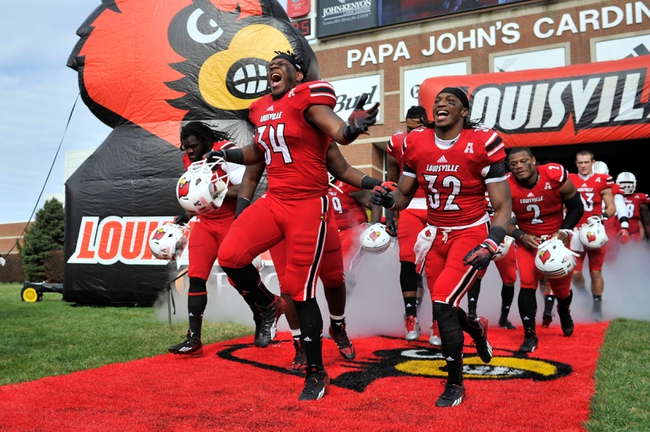 Nov 23, 2013; Louisville, KY, USA; Louisville Cardinals linebacker George Durant (34) and Louisville Cardinals running back Senorise Perry (32) lead the team onto the field before the first  quarter against the Memphis Tigers at Papa Johns Cardinal Stadium. Louisville defeated Memphis 24-17.  Mandatory Credit: Jamie Rhodes-USA TODAY Sports