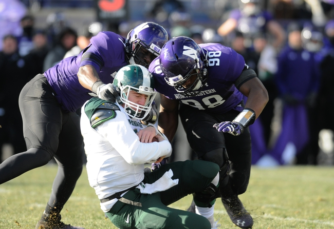 Nov 23, 2013; Evanston, IL, USA; Michigan State Spartans quarterback Connor Cook (18) is sacked by Northwestern Wildcats defensive lineman Deonte Gibson (98) and defensive lineman Ifeadi Odenigbo (7) during the second half at Ryan Field. Michigan State won 30-6. Mandatory Credit: Reid Compton-USA TODAY Sports