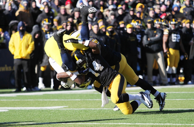 Nov 23, 2013; Iowa City, IA, USA; Michigan Wolverines tight end Devin Funchess (87) is tackled by Iowa Hawkeyes cornerback Desmond King (14) and linebacker Anthony Hitchens (31) at Kinnick Stadium. Iowa beat Michigan 24-21.  Mandatory Credit: Reese Strickland-USA TODAY Sports