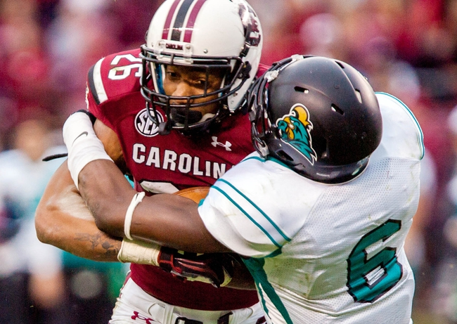 Nov 23, 2013; Columbia, SC, USA; South Carolina Gamecocks running back Jamari Smith (26) is brought down by Coastal Carolina Chanticleers defensive back Pernell Williams (6) in the second half at Williams-Brice Stadium. Mandatory Credit: Jeff Blake-USA TODAY