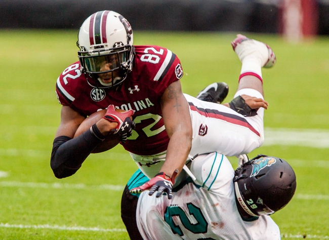 Nov 23, 2013; Columbia, SC, USA; South Carolina Gamecocks wide receiver Kwinton Smith (82) dives over Coastal Carolina Chanticleers defensive back Kamron Summers (29) in the second half at Williams-Brice Stadium. Mandatory Credit: Jeff Blake-USA TODAY