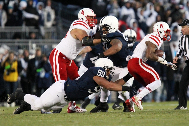 Nov 23, 2013; University Park, PA, USA; Penn State Nittany Lions defensive tackle Austin Johnson (99) attempts to tackle Nebraska Cornhuskers running back Ameer Abdullah (8) during the second quarter against the Nebraska Cornhuskers at Beaver Stadium. Mandatory Credit: Matthew O'Haren-USA TODAY Sports