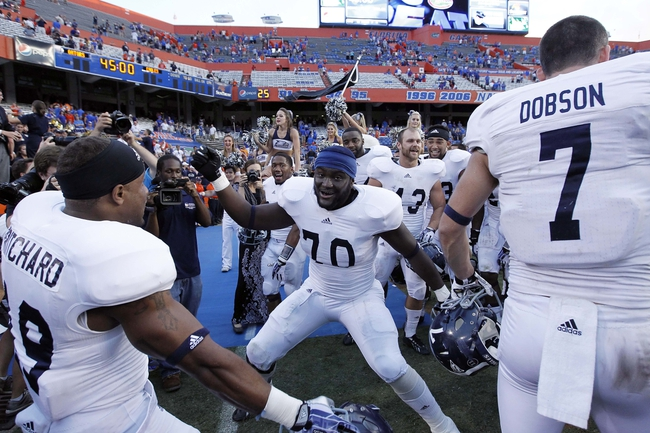 Nov 23, 2013; Gainesville, FL, USA; Georgia Southern Eagles offensive tackle Raymond Klugey (70), defensive back Travosier Mitchell (19) and teammates celebrate after they beat the Florida Gators at Ben Hill Griffin Stadium. Georgia Southern Eagles defeated the Florida Gators 26-20. Mandatory Credit: Kim Klement-USA TODAY Sports