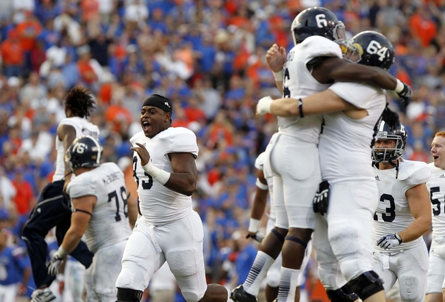 Nov 23, 2013; Gainesville, FL, USA; Georgia Southern Eagles defensive end Rashad Williams (93) and teammates celebrate after they beat the Florida Gators at Ben Hill Griffin Stadium. Georgia Southern Eagles defeated the Florida Gators 26-20. Mandatory Credit: Kim Klement-USA TODAY Sports