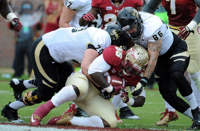Nov 23, 2013; Tallahassee, FL, USA; Florida State Seminoles defensive tackle Jacobbi McDaniel (55) is tackled after intercepting the ball by Idaho Vandals offensive lineman Niklaus Von Rotz (70) and tight end Michael LaGrone (86) during the first half at Doak Campbell Stadium. Mandatory Credit: Melina Vastola-USA TODAY Sports