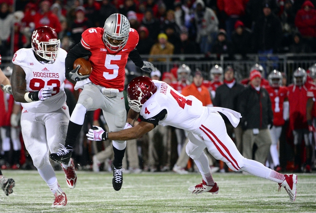 Nov 23, 2013; Columbus, OH, USA; Ohio State Buckeyes quarterback Braxton Miller (5) jumps to avoid being tackled by Indiana Hoosiers linebacker Forisse Hardin (4) during the second half of the game at Ohio Stadium. Mandatory Credit: Marc Lebryk-USA TODAY Sports