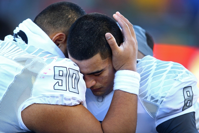Nov 23, 2013; Tucson, AZ, USA; Oregon Ducks quarterback Marcus Mariota (right) is consoled by defensive tackle Ricky Havili-Heimuli after suffering an injury in the fourth quarter against the Arizona Wildcats at Arizona Stadium. Arizona defeated Oregon 42-16. Mandatory Credit: Mark J. Rebilas-USA TODAY Sports