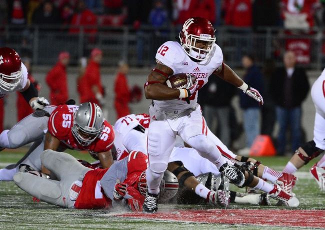 Nov 23, 2013; Columbus, OH, USA;  Indiana Hoosiers running back Stephen Houston (12) evades a tackle during the second half of the game at Ohio Stadium. Ohio State Buckeyes beat the Indiana Hoosiers 42 to 14. Mandatory Credit: Marc Lebryk-USA TODAY Sports