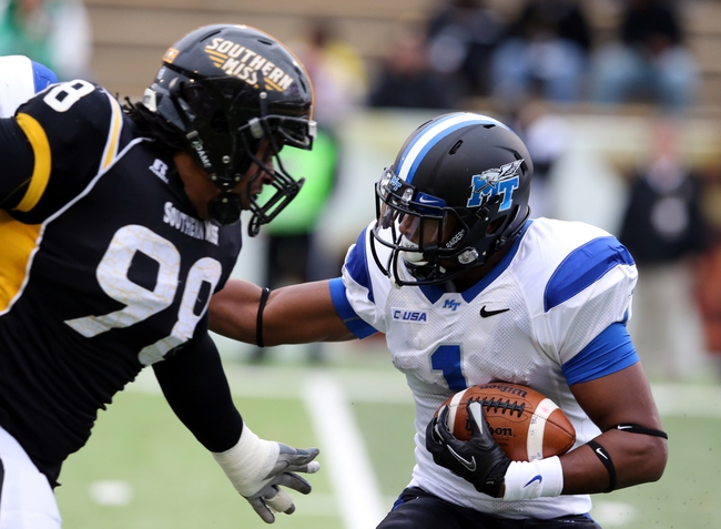 Nov 23, 2013; Hattiesburg, MS, USA; Middle Tennessee Blue Raiders running back Shane Tucker (1) is tackled by Southern Miss Golden Eagles defensive lineman Khyri Thornton (98) in the first quarter of their game at M.M. Roberts Stadium. Mandatory Credit: Chuck Cook-USA TODAY Sports