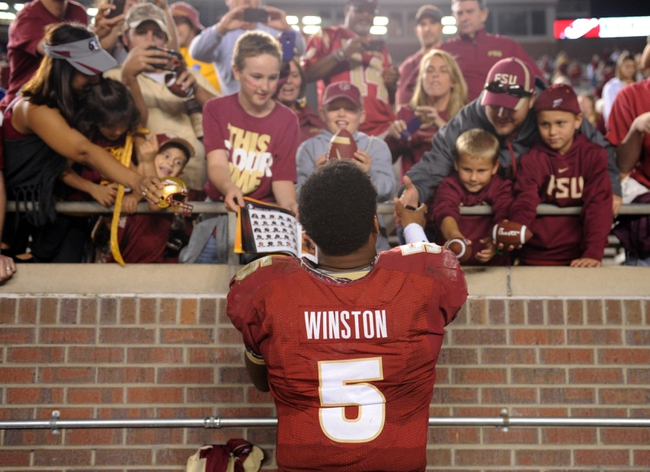 Nov 23, 2013; Tallahassee, FL, USA; Florida State Seminoles quarterback Jameis Winston (5) signs autographs for fans after the game against the Idaho Vandals at Doak Campbell Stadium. Mandatory Credit: Melina Vastola-USA TODAY Sports