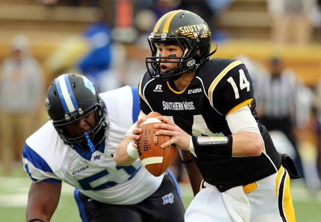 Nov 23, 2013; Hattiesburg, MS, USA; Southern Miss Golden Eagles quarterback Nick Mullens (14) runs away from Middle Tennessee Blue Raiders defensive tackle Shaquille Huff (51) in the first quarter of their game at M.M. Roberts Stadium. Mandatory Credit: Chuck Cook-USA TODAY Sports
