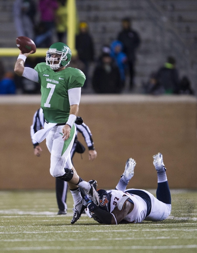 Nov 23, 2013; Denton, TX, USA; North Texas Mean Green quarterback Derek Thompson (7) eludes UTSA Roadrunners defensive tackle Ashaad Mabry (97) during the second half at Apogee Stadium. The Roadrunners defeated the Mean Green 21-13. Mandatory Credit: Jerome Miron-USA TODAY Sports