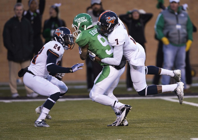 Nov 23, 2013; Denton, TX, USA; North Texas Mean Green wide receiver Carlos Harris (9) is tackled by UTSA Roadrunners cornerback Darrien Starling (24) and safety Triston Wade (7) during the second half at Apogee Stadium. The Roadrunners defeated the Mean Green 21-13. Mandatory Credit: Jerome Miron-USA TODAY Sports