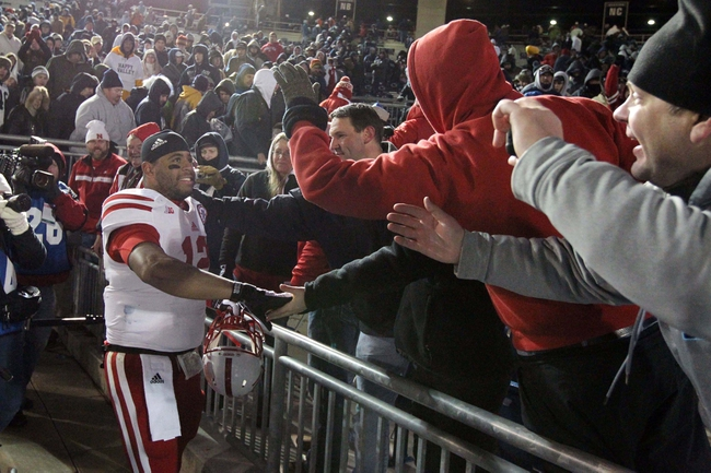 Nov 23, 2013; University Park, PA, USA; Nebraska Cornhuskers quarterback Ron Kellogg III (12) shakes the hands of fans after the completion of the game against the Penn State Nittany Lions at Beaver Stadium. Nebraska defeated Penn State 23-20 in overtime. Mandatory Credit: Matthew O'Haren-USA TODAY Sports