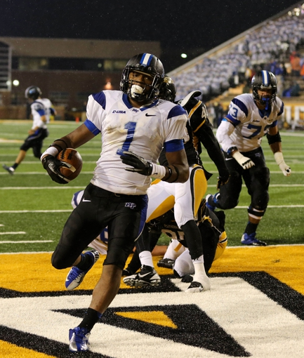 Nov 23, 2013; Hattiesburg, MS, USA; Middle Tennessee Blue Raiders running back Shane Tucker (1) scores on a 4-yard run in the second half of their game against the Southern Miss Golden Eagles at M.M. Roberts Stadium. Middle Tennessee won, 42-21. Mandatory Credit: Chuck Cook-USA TODAY Sports
