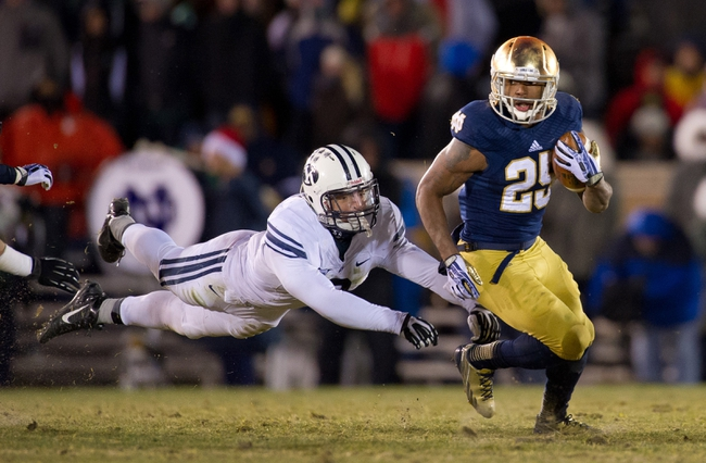 Nov 23, 2013; South Bend, IN, USA; Notre Dame Fighting Irish running back Tarean Folston (25) carries the ball as BYU Cougars linebacker Kyle Van Noy (3) attempts to tackle in the fourth quarter at Notre Dame Stadium. Notre Dame won 23-13. Mandatory Credit: Matt Cashore-USA TODAY Sports