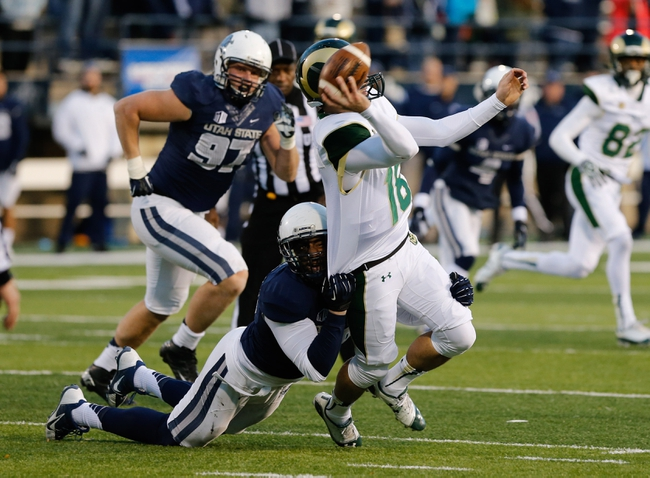 Nov 23, 2013; Logan, UT, USA; Colorado State Rams quarterback Garrett Grayson (18) throws the ball as he is being pulled down by Utah State Aggies defensive end Paul Piukala (48) during the fourth quarter at Romney Stadium. Utah State Aggies won 13-0. Mandatory Credit: Chris Nicoll-USA TODAY Sports