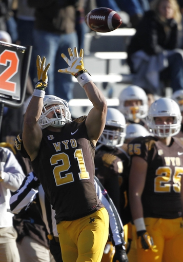 Nov 23, 2013; Laramie, WY, USA; Wyoming Cowboys running back Shaun Wick (21) makes a catch against the Hawaii Warriors during the third quarter at War Memorial Stadium. The Cowboys defeated the Warriors 59-56 in overtime. Mandatory Credit: Troy Babbitt-USA TODAY Sports