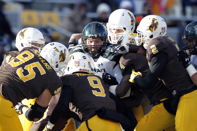 Nov 23, 2013; Laramie, WY, USA; Hawaii Warriors tight end Clark Evans (84)is tackled by the Wyoming Cowboys defensive during the third quarter at War Memorial Stadium. The Cowboys defeated the Warriors 59-56 in overtime. Mandatory Credit: Troy Babbitt-USA TODAY Sports