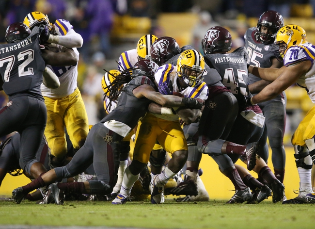 Nov 23, 2013; Baton Rouge, LA, USA; LSU Tigers running back Alfred Blue (4) is tackled by Texas A&M Aggies defensive back Floyd Raven Sr. (left) as he carries the ball in the second half at Tiger Stadium. LSU defeated Texas A&M 34-10. Mandatory Credit: Crystal LoGiudice-USA TODAY Sports