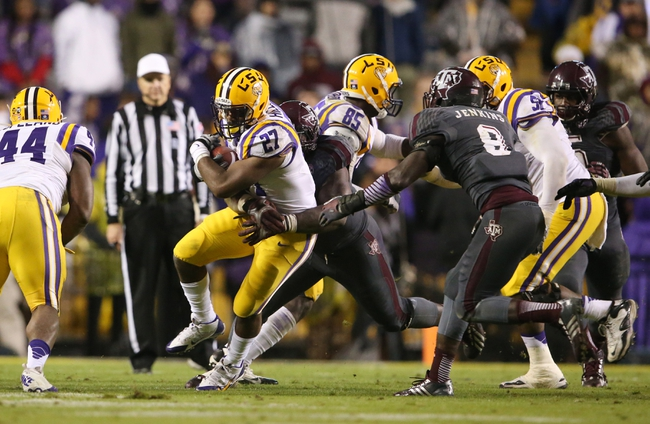 Nov 23, 2013; Baton Rouge, LA, USA; LSU Tigers running back Kenny Hilliard (27) is tackled from behind by Texas A&M Aggies defensive lineman Ivan Robinson (behind) as he carries the ball in the second half at Tiger Stadium. LSU defeated Texas A&M 34-10. Mandatory Credit: Crystal LoGiudice-USA TODAY Sports