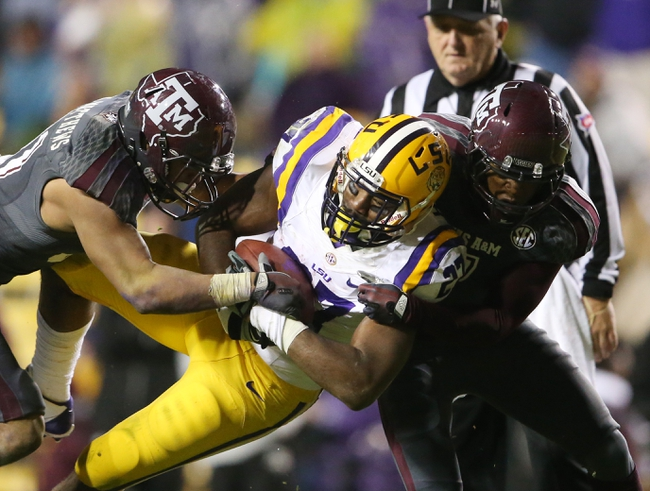 Nov 23, 2013; Baton Rouge, LA, USA; LSU Tigers running back Kenny Hilliard (27) is tackled by Texas A&M Aggies defensive back Howard Matthews (left) and Texas A&M Aggies defensive back Tramain Jacobs (7) in the second half at Tiger Stadium. LSU defeated Texas A&M 34-10. Mandatory Credit: Crystal LoGiudice-USA TODAY Sports
