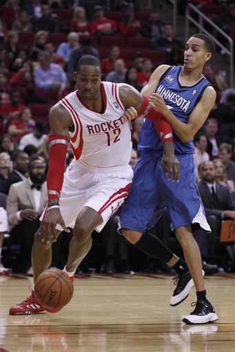 Nov 23, 2013; Houston, TX, USA; Houston Rockets power forward Dwight Howard (12) is fouled by Minnesota Timberwolves shooting guard Kevin Martin (23) during the second quarter at Toyota Center. Mandatory Credit: Andrew Richardson-USA TODAY Sports