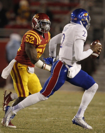 Nov 23, 2013; Ames, IA, USA; Iowa State Cyclones defender Jeremiah George (52) chases Kansas Jayhawks quarterback Montell Cozart (2) in the second quarter at Jack Trice Stadium. Mandatory Credit: Bruce Thorson-USA TODAY Sports