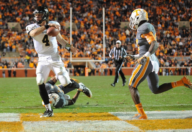 Nov 23, 2013; Knoxville, TN, USA; Vanderbilt Commodores quarterback Patton Robinette (4) scores the game winning touchdown with 16 seconds left in the game against Tennessee Volunteers defensive back Brian Randolph (37) at Neyland Stadium. Vanderbilt won 14 to 10. Mandatory Credit: Randy Sartin-USA TODAY Sports